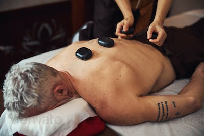 Man during back massage with stones in studio