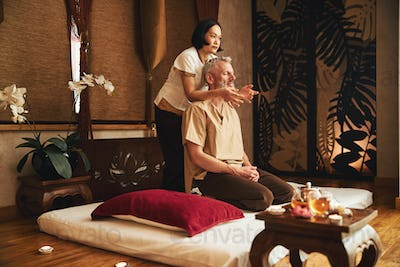 Asian woman doing traditional massage for grizzled man