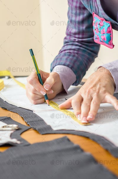 Dressmaker drawing tailor pattern on the table