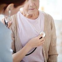 Caring nurse using stethoscope while examining retired woman
