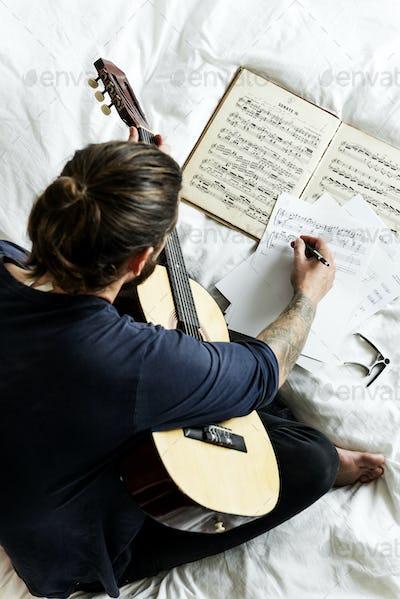 Man playing guitar composing