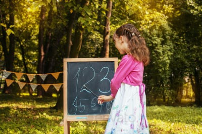 Little schoolgirl teaches numbers near the blackboard. Back to school. The concept of education