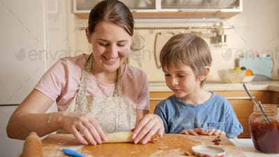 Young mother teaching her little son baking sweet roll with jam filling. Children cooking with