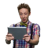 Extremely surprised teenage boy's looking at tablet pc screen.