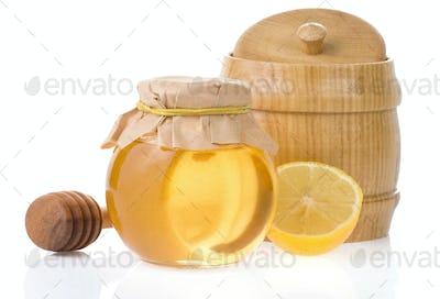 jar of honey and lemon isolated on white