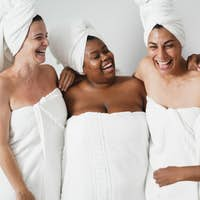 Multigeneration women with diverse skin and body laughing together while wearing body towels