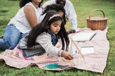Indian parents having fun painting with children outdoor at city park - Main focus on girl face