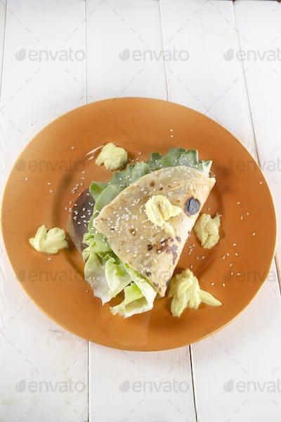 Vegan cuisine presentation of a mayonnaise and salad flatbread