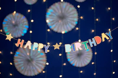 Happy birthday garland and decorations on blue background