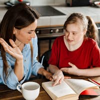 White woman helping her daughter with down syndrome reading book