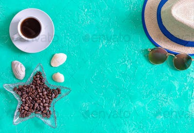 Cup of coffee, roasted coffee beans, hat and sunglasses. Top view, flat lay. Sea style.