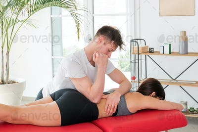 Osteopath doing a square myofascial massage of the loins