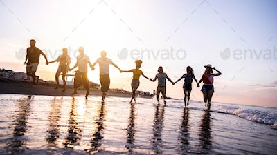 Group of young people running at sunset beach