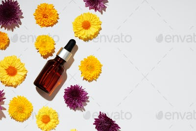 Cosmetic oil bottle on floral buds background