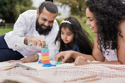 Happy indian parents and child having playful time at park