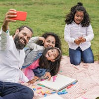 Happy indian family enjoy day outdoor at city park with pic nic and toys while taking a selfie