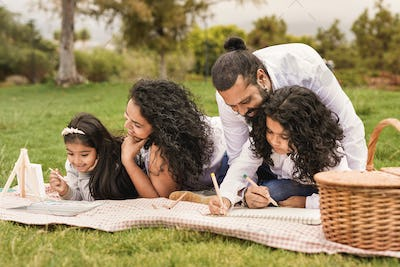 Happy indian family painting together at park - Family, parents and children love