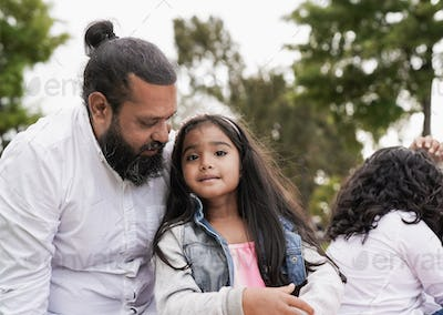 Indian family enjoy day at city park - Child sitting next to his father and looking in camera