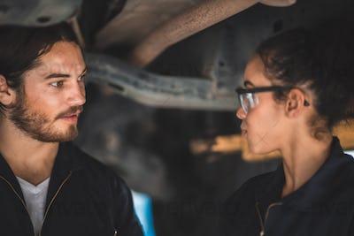 male and female machanic wearing uniform doing automoblie checklist