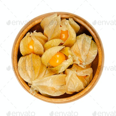 Cape gooseberries with partly open calyx, in a wooden bowl