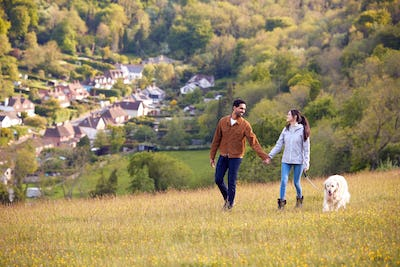 Couple With Pet Golden Retriever Dog Walking Along Path Across Field In Countryside