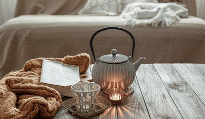 Cozy home composition with tea and a book in the interior of the room.