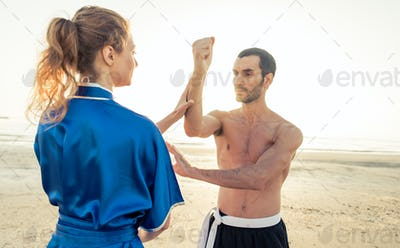 Couple of students training martial arts on the beach