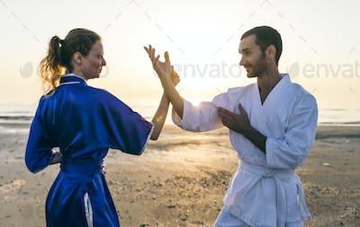 Couple training martial arts on the beach