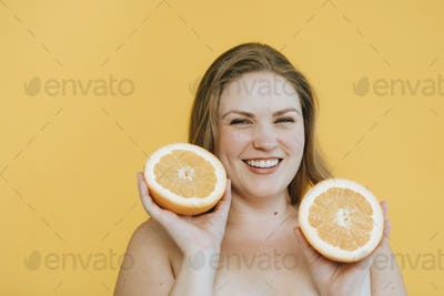 Blond woman holding two fresh oranges