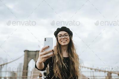 Cheerful woman taking a selfie with The Brooklyn Bridge, USA