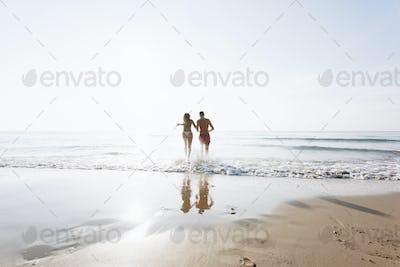 Cheerful couple running at the beach