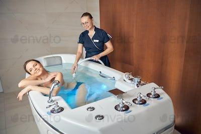 Joyful woman lying in a hydromassage bathtub