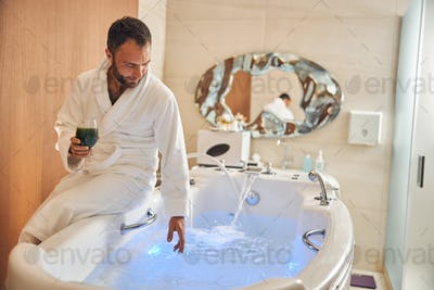 Handsome young man sitting on edge of bathtub