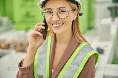 Smiling female engineer talking on her smartphone