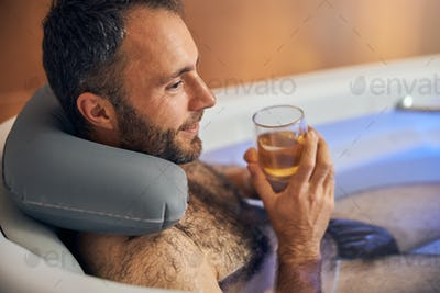 Cheerful young man taking bath and drinking wine