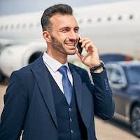 Businessman talking on the phone near an airplane