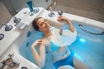 Happy pretty woman enjoying a hydrotherapy procedure
