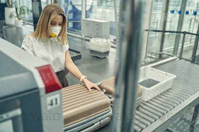 Concentrated young woman looking at her suitcase