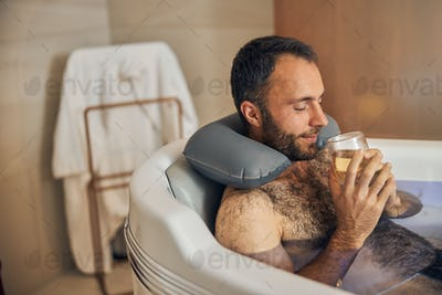 Handsome young man taking bath and drinking juice