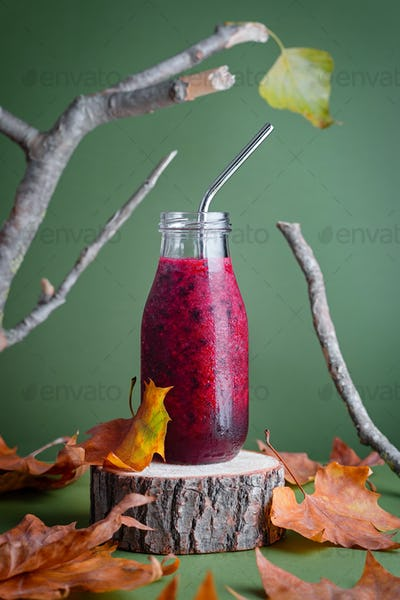 Immune system boosting red berries smoothie on wooden stand with leaves for autumn or virus season