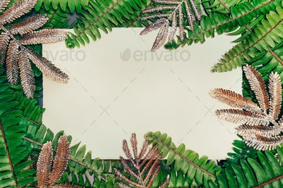 Natural green fern and golden leaves with empty paper card and free copy space