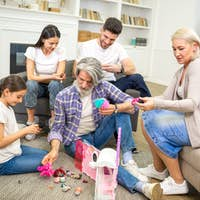 Happy family having nice time playing with little girl and her dollhouse