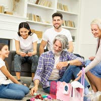 Big family having fun time together playing with child and her dollhouse