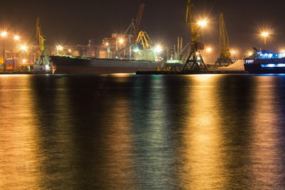 Cargo vessel is moored at container terminal at night