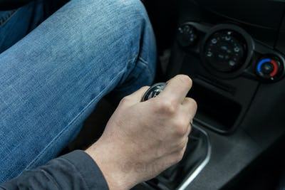 man's Hand Changing Gear While Driving