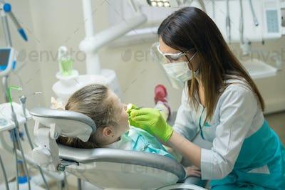 Female Dentist checking little girl patient