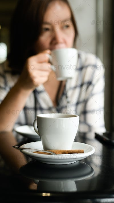 A white coffee mug is placed on the table, a young woman sits drinking coffee in the background.