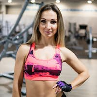 Fitness trainer looks into the camera in the gym