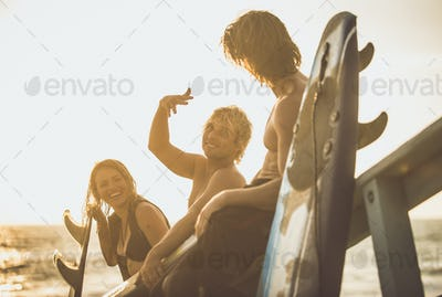 Three surfers relaxing on the beach after sport