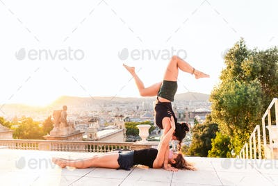 Two beautiful women doing acroyoga in the city
